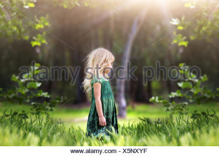 Girl (4-5) standing in meadow - Stock Photo