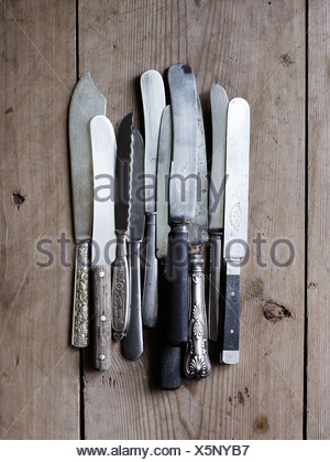 Scandinavia, Sweden, Knives on wooden background, close-up - Stock Photo