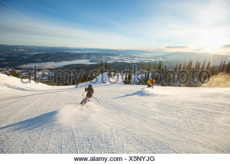 Two people on ski slope at sunlight - Stock Photo