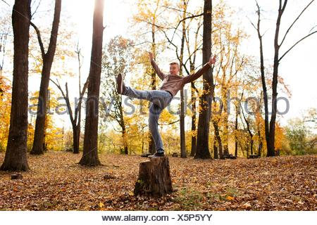 Teenage boy balancing on tree stump in autumn forest - Stock Photo