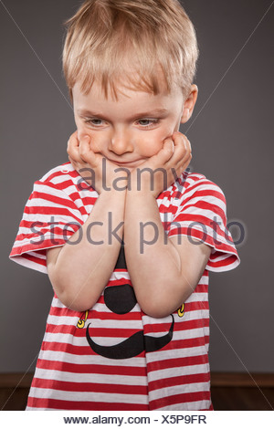 Portrait of little boy holding head in his hands - Stock Photo