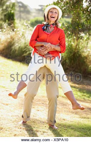 Senior Couple Having Fun Together In Garden - Stock Photo