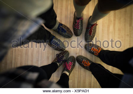 Overhead friends in bowling shoes in a circle - Stock Photo