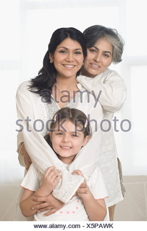 Portrait of a mature woman with her daughter and granddaughter smiling - Stock Photo