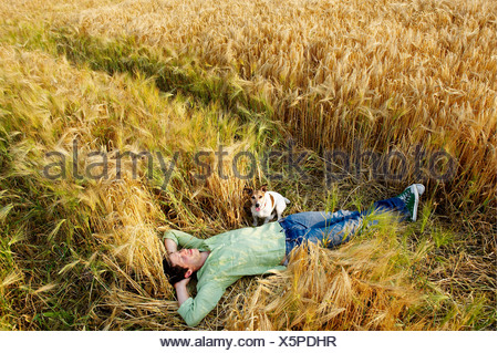 Man with dog laying down in wheat field - Stock Photo