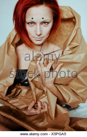 Red haired woman in craft paper - Stock Photo