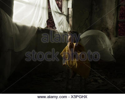 Girl sitting on a chair looking out of a window in an abandoned house - Stock Photo