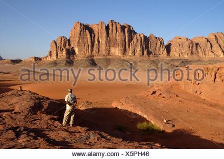 single man standing on a rock looking at the desert Wadi Rum, Jordan - Stock Photo