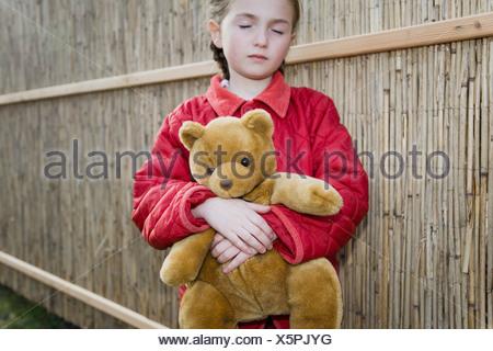 A young girl holding a teddy bear - Stock Photo