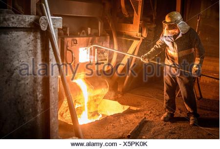 Steel worker and molten metal in steel foundry