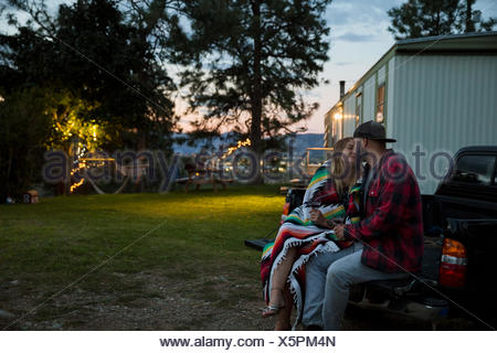 Affectionate couple kissing at truck bed outside trailer home at night - Stock Photo