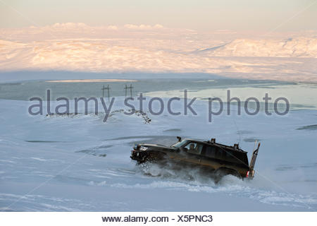 Super Jeep driving at full throttle up a steep snowy slope, Hrauneyjar, Iceland, Europe - Stock Photo