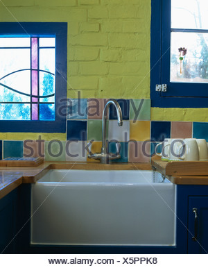 Close-up of colorful tiles on wall above steel mixer tap and Belfast sink in yellow kitchen - Stock Photo