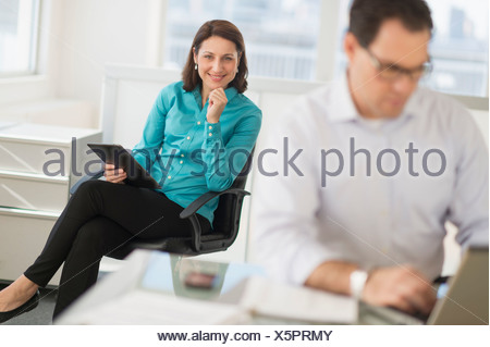Businessman and businesswoman working in office - Stock Photo