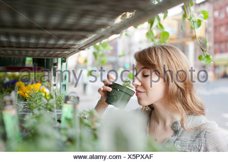 Young woman smelling a plant - Stock Photo