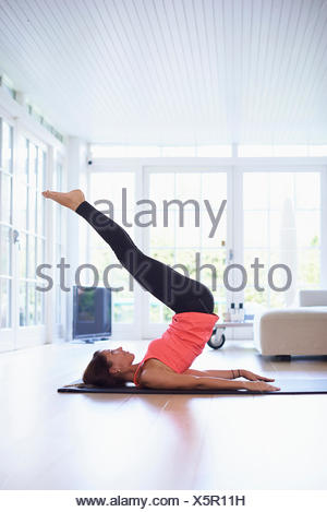 Mid adult woman lying on back practicing yoga in living room - Stock Photo