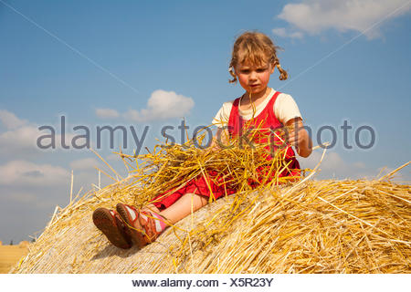 Little girl sitting on a straw bale under a cloudy blue sky, Germany - Stock Photo