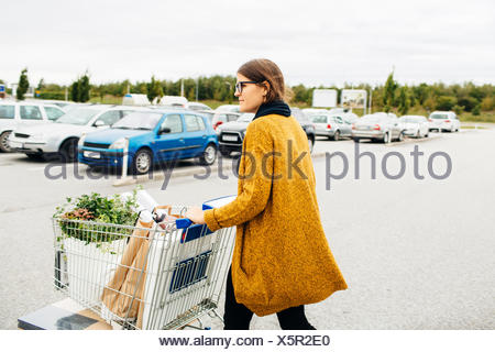 Side view of young woman pushing trolley full of purchases towards car park - Stock Photo
