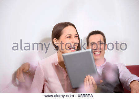 Young couple holding tablet computer laughing - Stock Photo