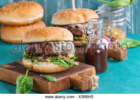 Two hamburgers with beef burger cutlet, fried onion, spinach, ketchup sauce and blue cheese in traditional buns, served on wood chopping board over br - Stock Photo