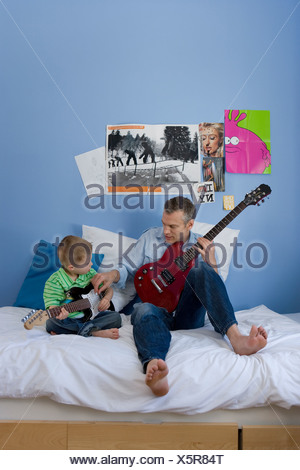 Father an son 2-4 on bed with electric guitars - Stock Photo