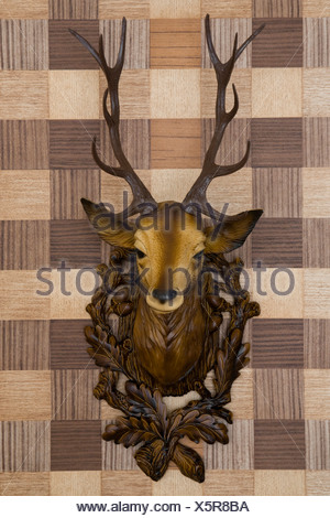 Plastic deer head mounted on imitation wood wallpaper, frontal view - Stock Photo