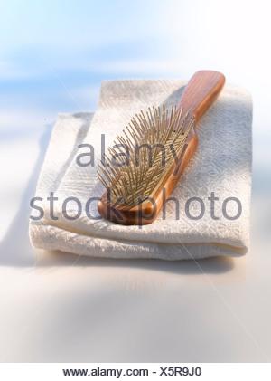 Hairbrush on white towel, close up - Stock Photo