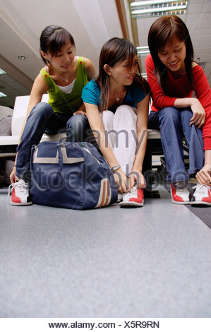 Women sitting, putting on bowling shoes - Stock Photo