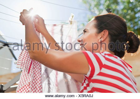 Woman hanging clothes up on line - Stock Photo