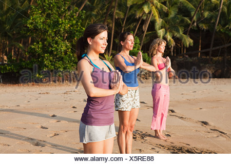 Women practicing yoga on a beach - Stock Photo