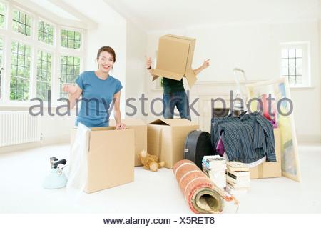 A couple having fun moving home - Stock Photo