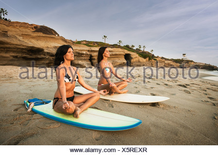 Two surfers, sitting on surfboards on beach, meditating - Stock Photo