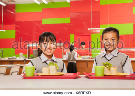 Two girls sitting in school cafeteria - Stock Photo