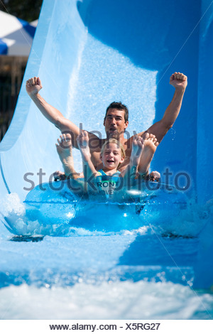 Father and daughter sliding down waterslide on innertube in waterpark - Stock Photo
