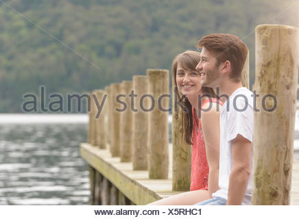 Young couple laughing together on jetty over lake - Stock Photo