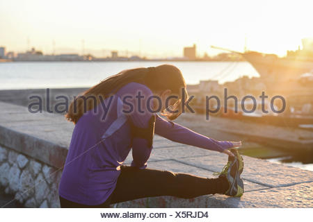 Young woman stretching her leg on a wall at sunset - Stock Photo