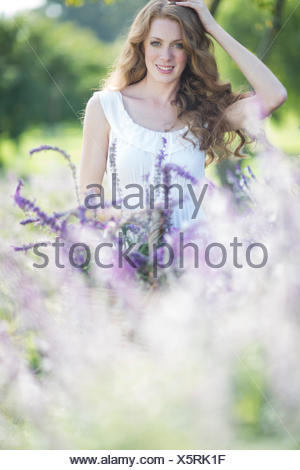 Portrait of beautiful young woman in meadow of purple flowers - Stock Photo