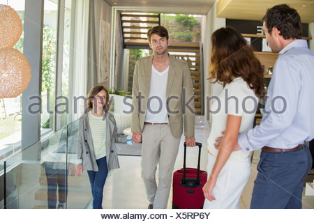 Man with his daughter arriving at his friends home from holiday - Stock Photo