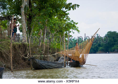 Casting A Net Into The Water Off The Edge Of A Boat On The Surma River In A Rural Area Near Sylhet; Bangladesh - Stock Photo