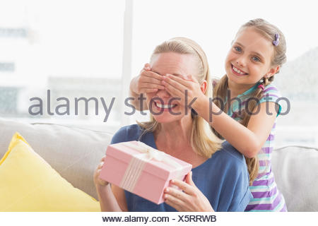 Mother holding gift with daughter covering her eyes - Stock Photo