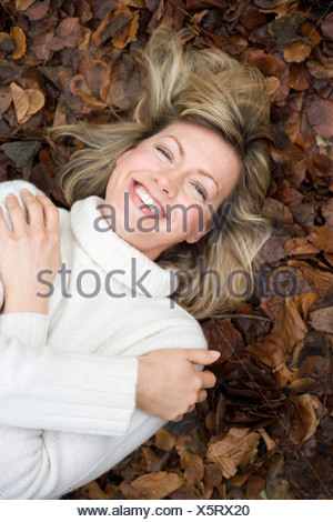 Smiling woman lying on autumn leaves. - Stock Photo