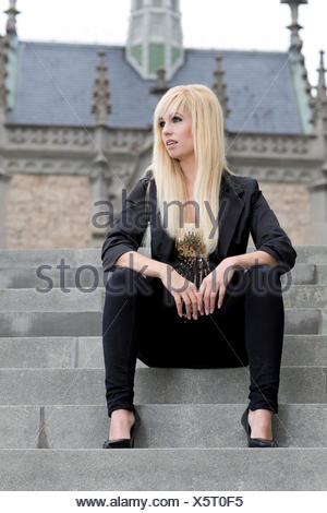 Young woman with long blond hair sitting on concrete stairs - Stock Photo