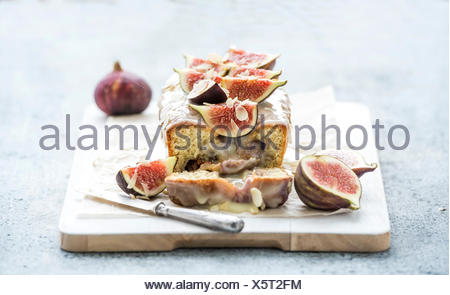 Loaf cake with figs, almond and white chocolate on white serving board over grunge background, selective focus - Stock Photo