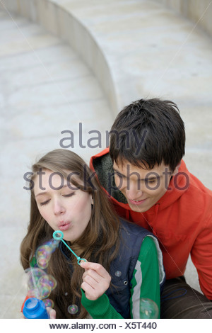 Young couple blowing soap bubbles - Stock Photo