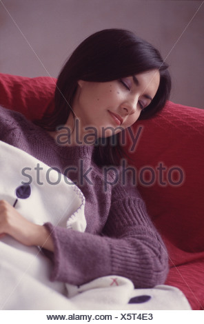 Female shoulder length straight black hair framing face wearing purple knitted jumper lying on red sofa covered in blue and - Stock Photo