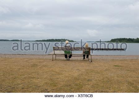 Children sitting on park bench beside lake - Stock Photo