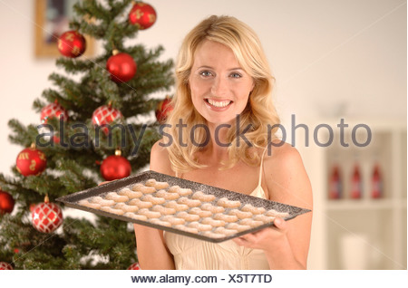 Blonde woman, 20-30, wearing an evening dress while holding a baking tray with Christmas cookies in front of a Christmas tree - Stock Photo
