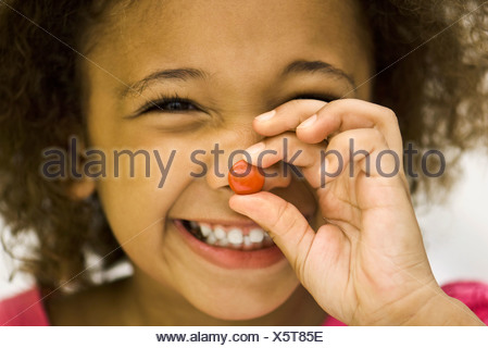 Little girl holding up piece of candy - Stock Photo