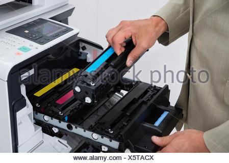 Businessman Fixing Cartridge In Photocopy Machine - Stock Photo