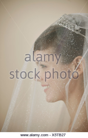A young bride wearing a tiara and veil smiling, side view - Stock Photo